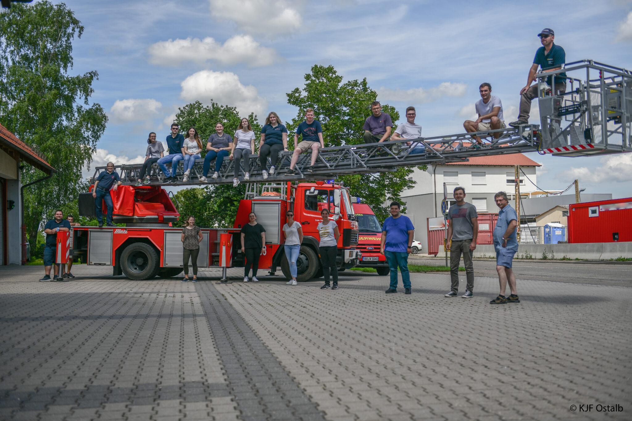 17 frisch gebackenen Jugendgruppenleiter und ihre Ausbilder vor der Drehleiter der Heubacher Feuerwehr.